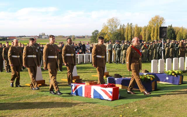 The coffin in laid down by soldiers