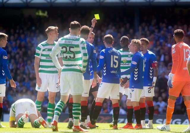 Jon Flanagan is booked during the Old Firm derby