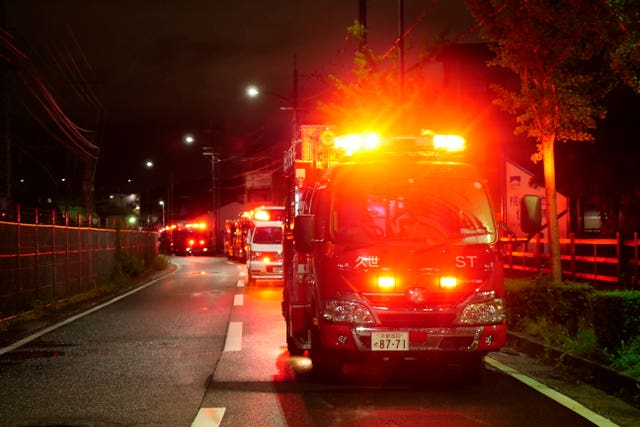 A fire engine stands by near the building of Kyoto Animation