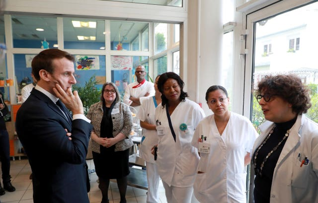 Emmanuel Macron meets  staff at a care home in Paris