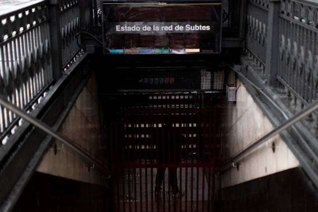An employee stands in the closed entrance of the Buenos Aires underground railway system during the blackout