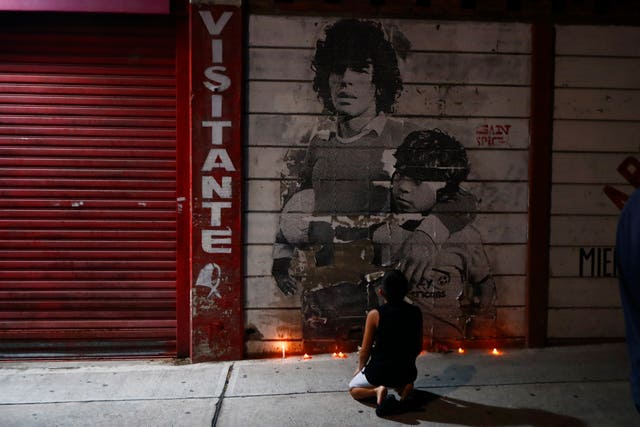A boy kneels in front of a mural of Diego Maradona outside the stadium of Argentinos Juniors