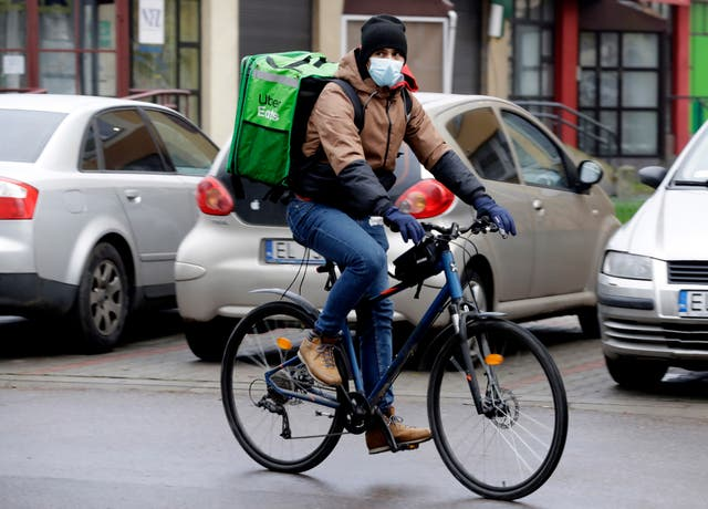 Venezuela's 2012 Olympic fencing champion Ruben Limardo Gascon cycles with a food delivery to clients in Lodz, Poland
