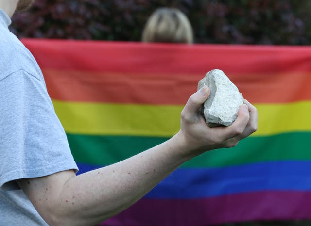 Someone holding a rock in front of a rainbow flag