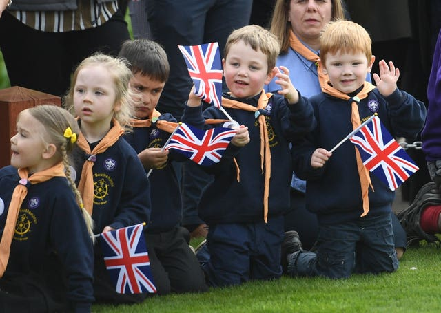 Children eagerly await the royal's arrival