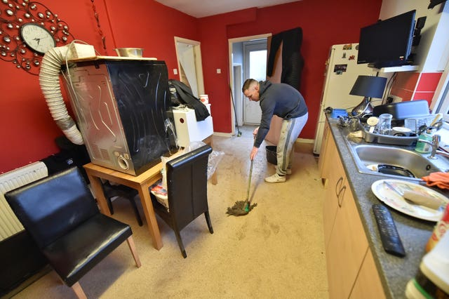 Lee Griffiths mopping the kitchen floor after flooding damaged his house on Rhyd-Yr-Helyg road in Nantgarw (Ben Birchall/PA)