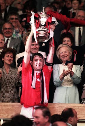 Manchester United captain Steve Bruce lifts the FA Cup trophy at Wembley after his side beat Chelsea 4-0 in the final
