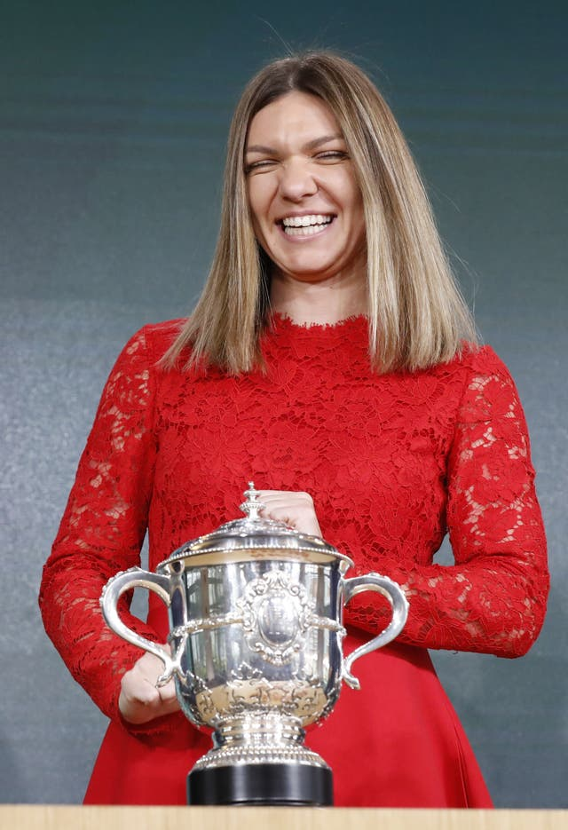 Defending champion Simona Halep is all smiles as she is reunited with the French Open trophy