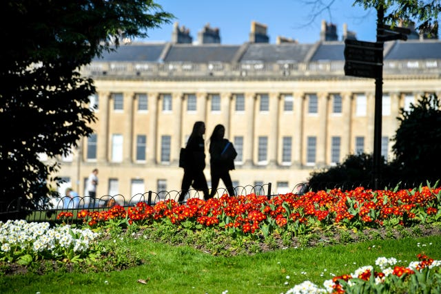 People pass colourful flowers in full bloom near the Royal Crescent, Bath