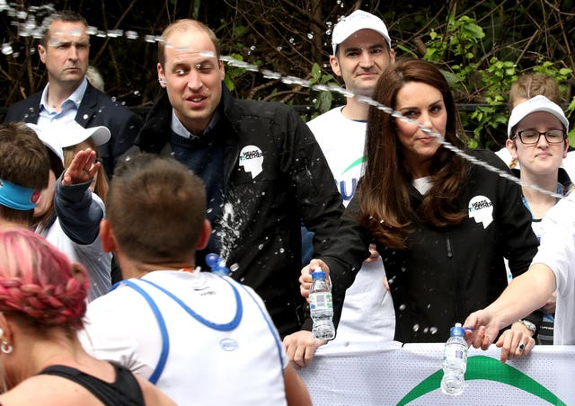 The Duke and Duchess of Cambridge hand out water to runners during the 2017 London Marathon