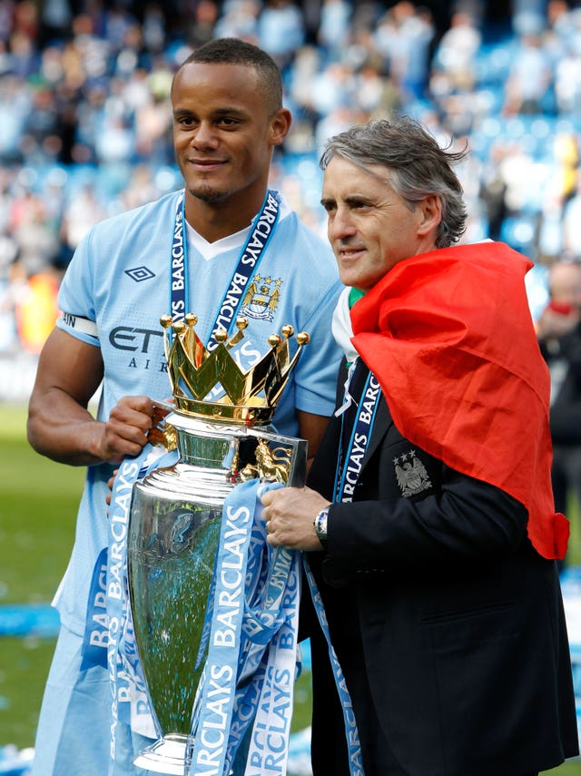 Vincent Kompany celebrates the 2012 Premier League title with manager Roberto Mancini