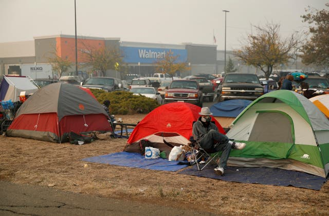 People sit by their tents at a makeshift encampment outside a Walmart store for people displaced by the Camp Fire