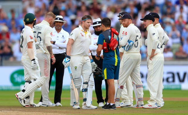 Steve Smith, centre, is assessed after being hit on the head