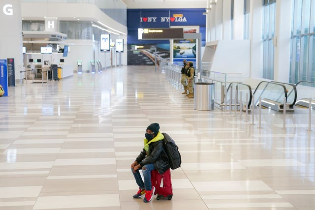 A traveller at Terminal C at LaGuardia Airport in the Queens borough of New York (John Minchillo/AP)