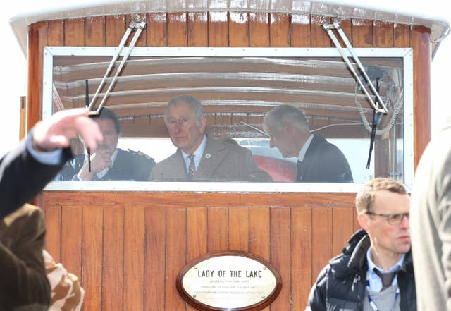The Prince of Wales takes the wheel in the boat house of the Lady Of The Lake (Peter Byrne/PA)