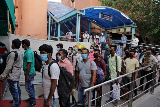 People queue for Covid-19 tests at a railway station in Ahmedabad, India