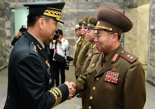 Major General Kim Do-gyun, left, shakes hands with Lieutenant General An Ik San