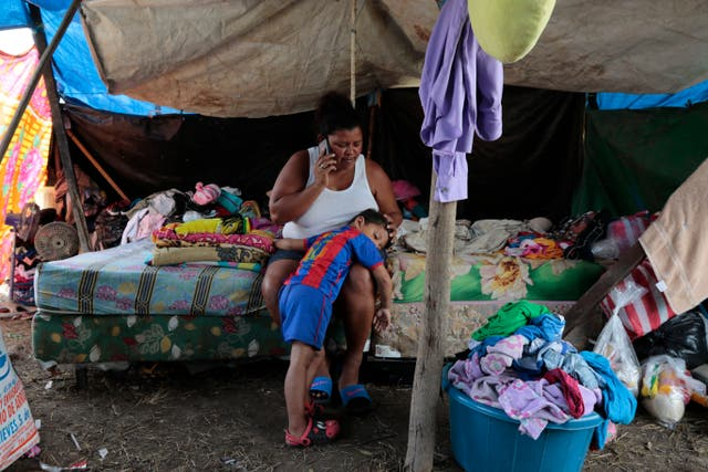 Wendy Guadalupe Contreras who was left homeless after the last storm hit the area, comforts her son as she speaks on the phone before Hurricane Iota makes landfall in La Lima, Honduras