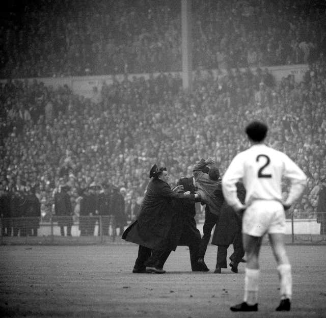 Leeds' Paul Reaney watches on as a Liverpool fan is apprehended for celebrating their winner