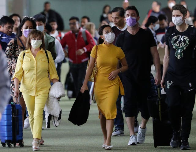 Passengers wear masks as they arrive at Manila's international airport
