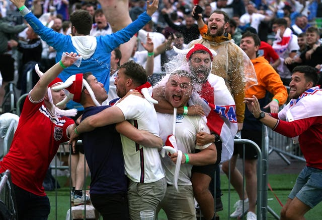 England supporters in Manchester celebrate as the team advance to the final four (Martin Rickett / PA).