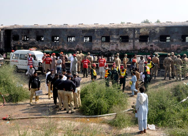 Soldiers and officials examine a train damaged by a fire in Liaquatpur, Pakistan
