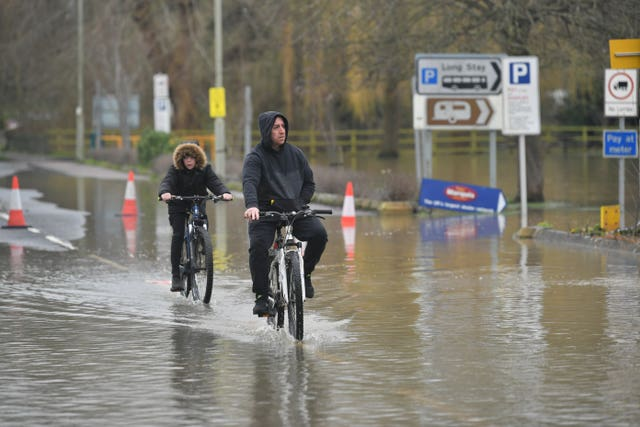 People riding their bikes through floodwater in Tewkesbury