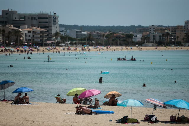 Sunbathers enjoy the beach in the Balearic Islands capital of Mallorca
