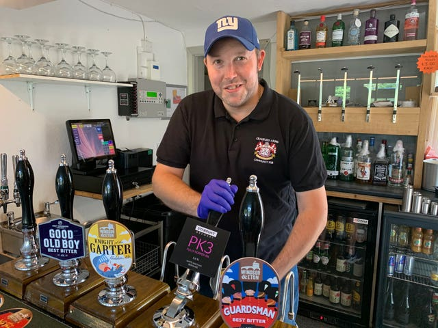 Neil Piddington, general manager of the Craufurd Arms community-owned pub in Maidenhead, checks the beer after Mr Johnson's announcement