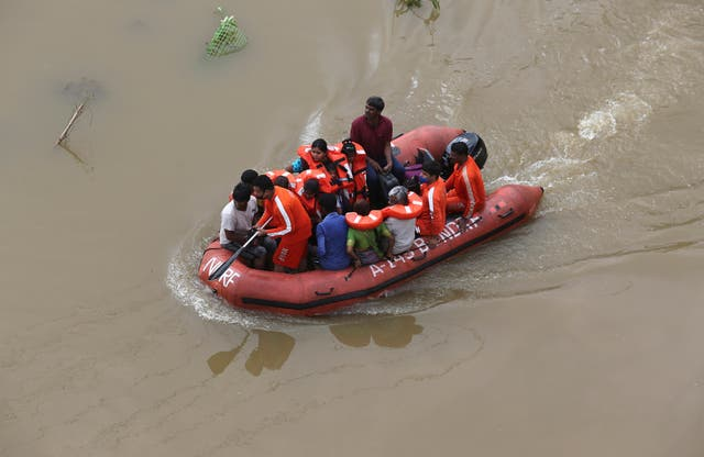 National Disaster Response Force (NDRF) personnel rescue people from floodwaters after heavy rainfall in Hyderabad, India (Mahesh Kumar A/AP)