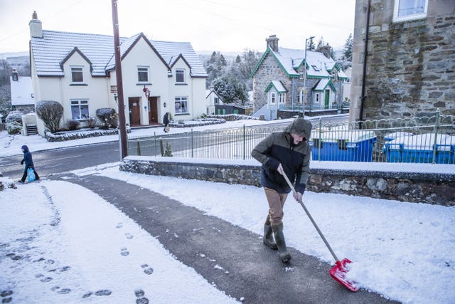 A man clears snow from a driveway in Killin, Stirlingshire