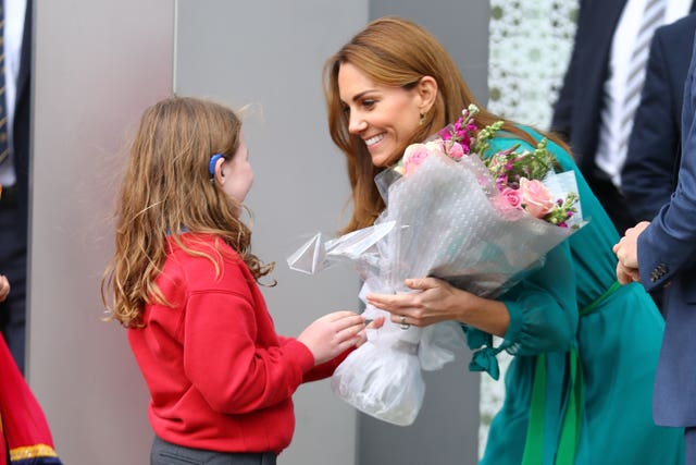The Duchess of Cambridge is presented with some flowers as she leaves a special event hosted by the Aga Khan ahead of their official visit to Pakistan