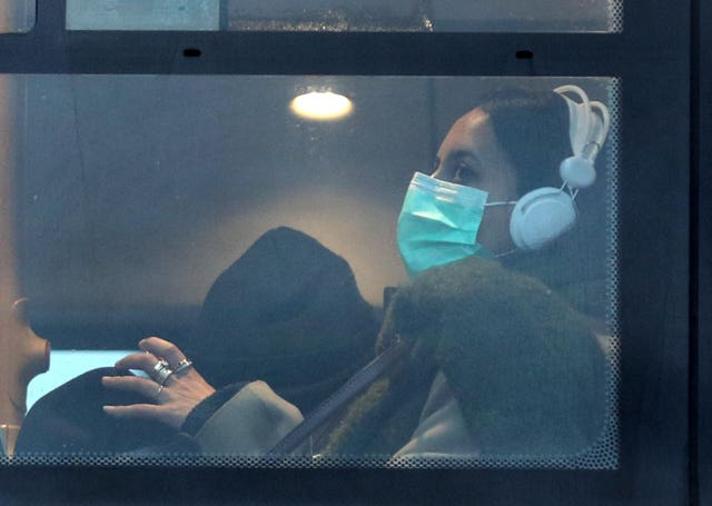 A woman wearing a face mask on a bus in London (Yui Mok/PA)