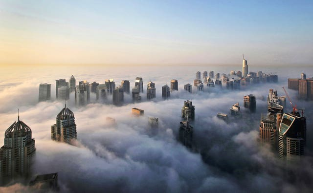 A thick blanket of early morning fog partially shrouds the skyscrapers of the Marina and Jumeirah Lake Towers districts of Dubai (Kamran Jemeili/AP)