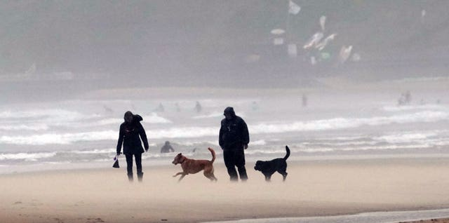 Walkers on a windy Tynemouth beach