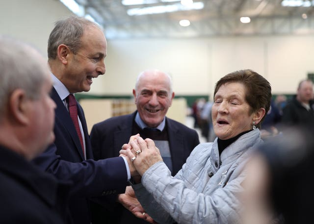 Fianna Fail leader Micheal Martin is greeted by a supporter during the Irish General Election count at the Nemo Rangers GAA Club in Cork