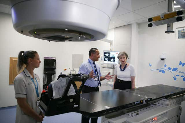 Theresa May is shown the advanced radiotherapy system during her visit to Addenbrooke's (Daniel Leal-Olivas/PA)