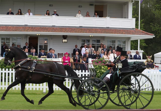 The Queen looks on as carriage drivers parade during in front of the royal box (Steve Parsons/PA)
