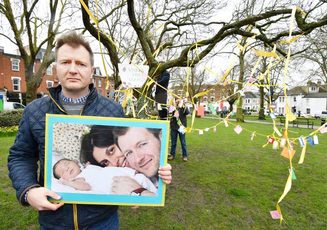 Richard Ratcliffe holds a photograph of himself with wife Nazanin and daughter Gabriella (John Stillwell/PA)