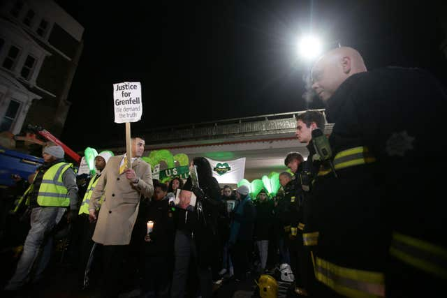 People pass firefighters paying their respects as they take part in a silent walk to mark the six month anniversary of the Grenfell Tower fire (Yui Mok/PA)