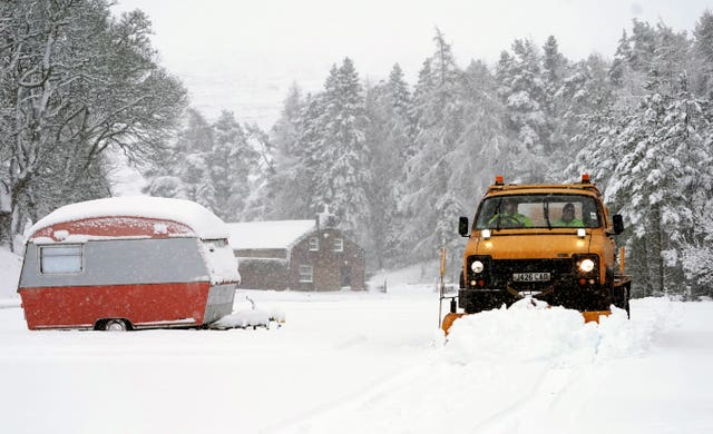 A snow plough passes an old caravan