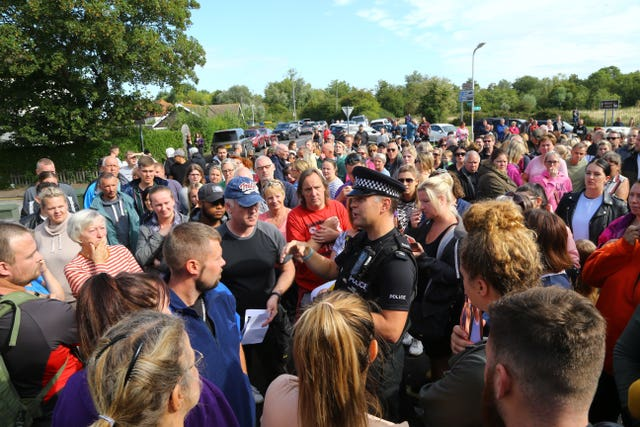 A police officer talks to members of the public gathered in Sandwich, Kent