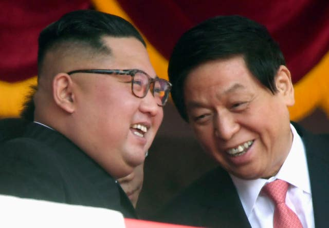 Kim Jong Un, left, smiles with China's third highest ranking official, Li Zhanshu
