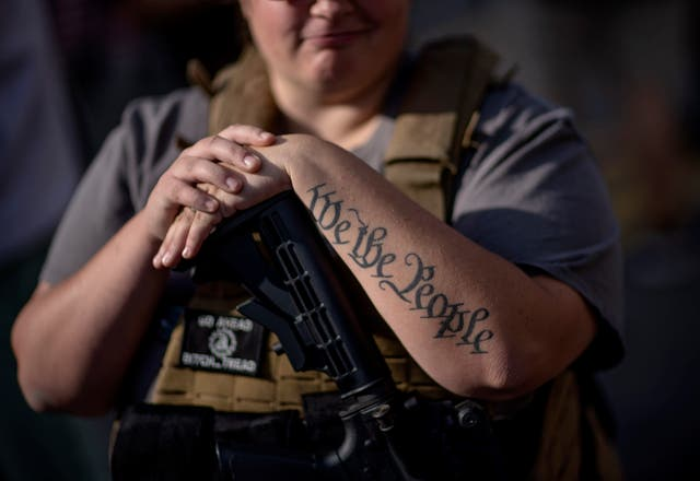 The tattoo saying 'We The People' decorates the arm of a Trump supporter as she rests her hand on her gun during a protest in Detroit