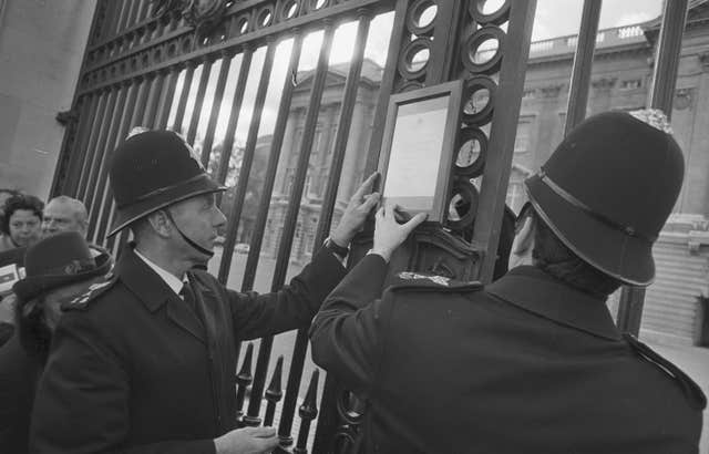 Policemen put up a bulletin signed by royal doctors on the gates of Buckingham Palace after the birth of Princess Anne's first child in 1977 (PA)