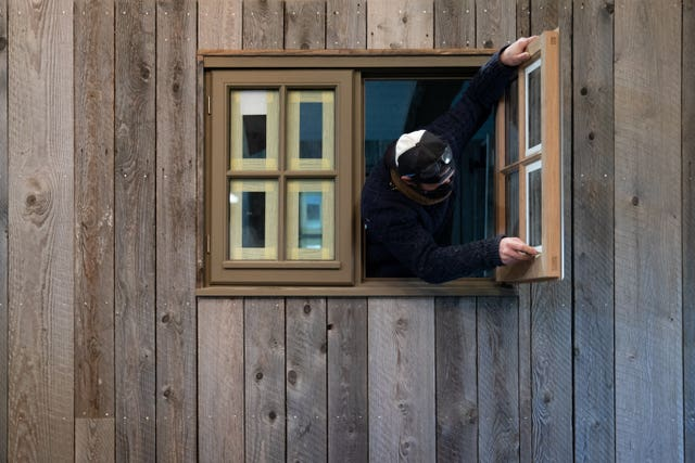 An employee removes tape from a window in a shepherd's hut in the workshop of Plankbridge