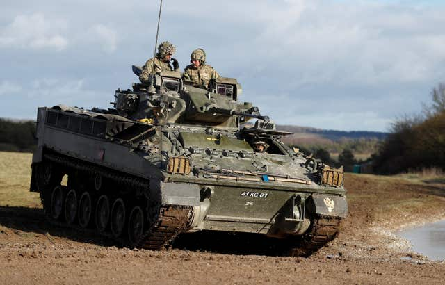 The Prince of Wales (back right) takes a ride on a Warrior infantry armoured vehicle during a visit to the Mercian Regiment to mark 10 years as its colonel-in-chief. (Peter Nicholls/PA)