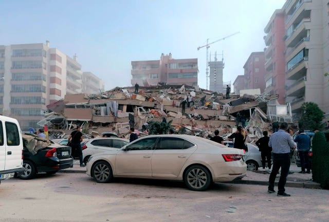 People work on a collapsed building in Izmir