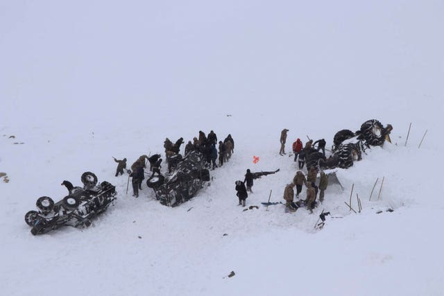 Emergency service members dig in the snow around overturned vehicles near the town of Bahcesehir in eastern Turkey