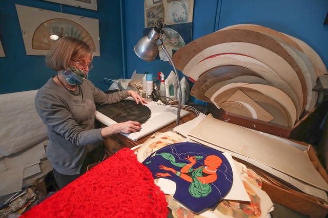 Anne Hoguet, 74, fan-maker and director of the hand fan-making museum works in her workshop in Paris, Wednesday, Jan. 20, 2021. Just like the leaves of its gilded fans, France's storied hand fan-making museum could fold up and vanish. The splendid Musee de l'Eventail in Paris, a classed historical monument, is the culture world's latest coronavirus victim
